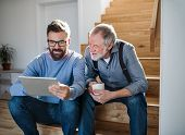 An Adult Son And Senior Father With Tablet Sitting On Stairs Indoors At Home. poster
