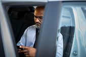 Senior african american businessman in formal clothing using cellphone while sitting on backseat in  poster