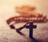 Cross and wooden rosary on stone background. Sunflare. Christian faith symbol. poster