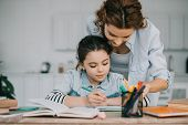 Adorable Child Writing In Copy Book While Doing Schoolwork Near Mother poster