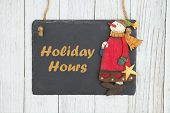 Holiday Hours Text With Chalkboard With A Snowman On Weathered Whitewash Textured Wood poster