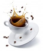 Splash of coffee in white cup and coffee beans in air. Isolated on white. poster
