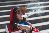 Vaping Girl. Young Woman With Skateboard Vape E-cig. Pretty Young Female In Black Hat, Red Clothing  poster