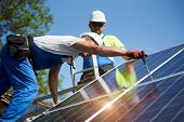 Two Professional Technicians Installing Solar Photo Voltaic Panel To Metal Platform On Blue Sky Back poster