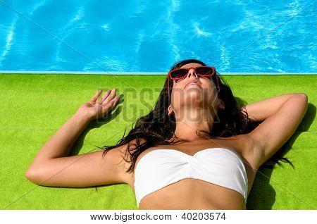 Morena, banhos de sol à beira da piscina