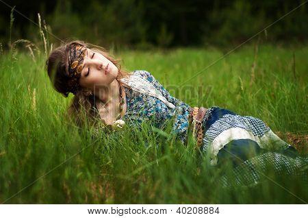 Hippie girl lies in the grass