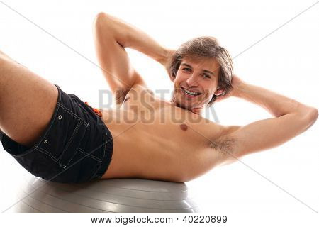 Handsome and sporty guy doing exercise for press over a white background