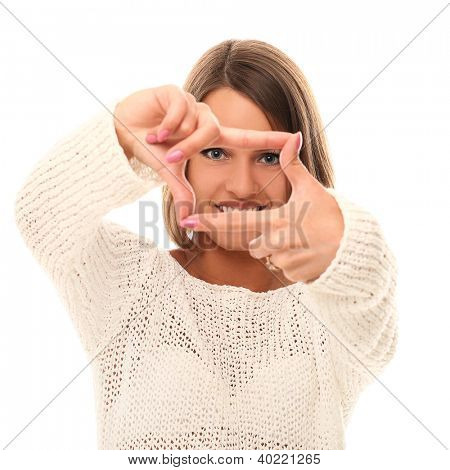 Young woman watching through frame fingers over a white