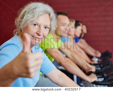 Smiling senior woman holding her thumbs up in spinning class in a fitness center