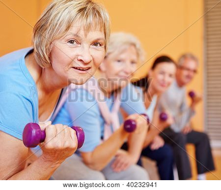 Senior woman with dumbbells doing back training in a fitness center