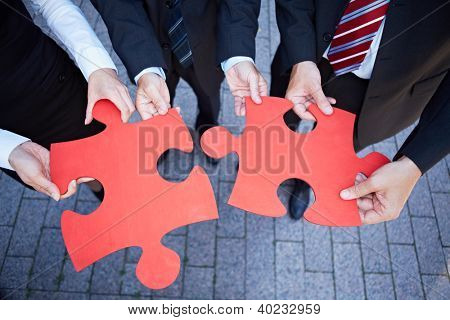 Business team hands holding two oversized red jigsaw puzzle pieces