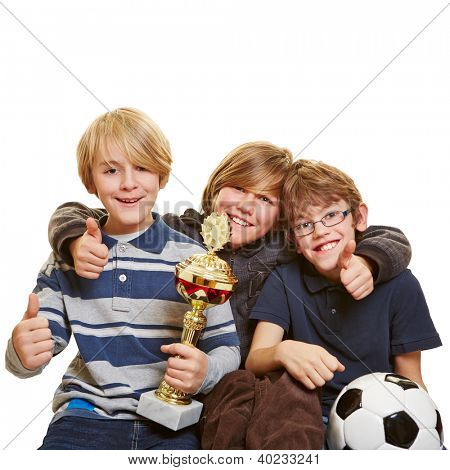 Successful kids with trophy and soccer ball holding their thumbs up