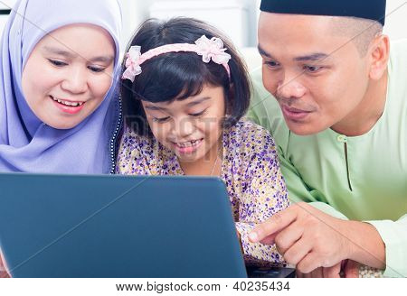 Southeast Asian family browsing internet at home. Muslim family living lifestyle