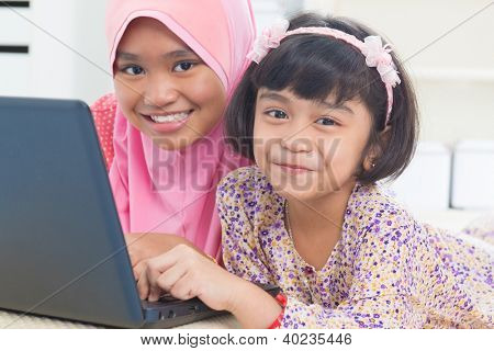 Southeast Asian children surfing internet at home. Malay Muslim girls