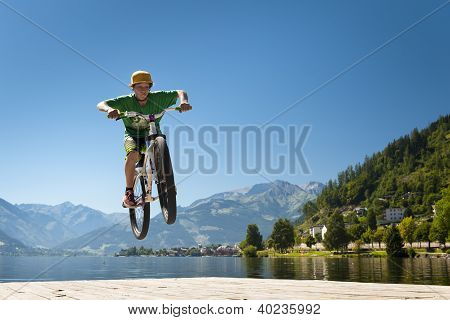 young male teenager jumps high with bike