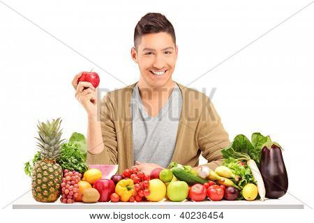 Handsome smiling guy holding an apple and posing on a table full of various vegetables and fruits isolated on white