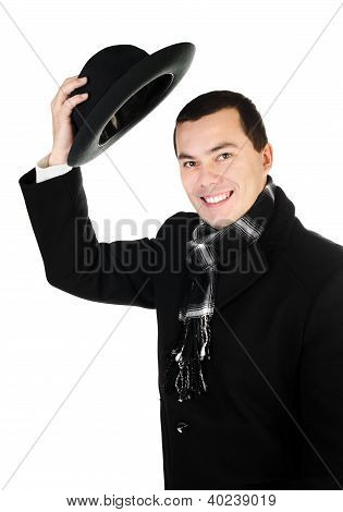 Smiling Young Man In Black Coat And Scarf Holding The Hat Isolated