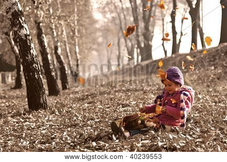 cute girl sitting on fallen autumn leaves while leafs falling and playing with dolls