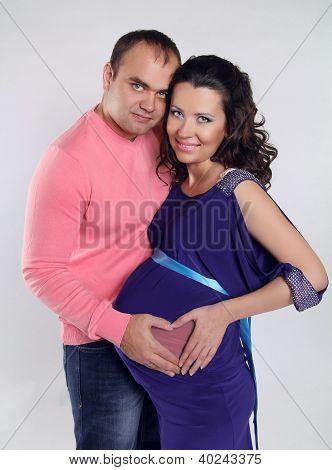 Portrait Of Happy Young Man Touching His Pregnant Wife Belly