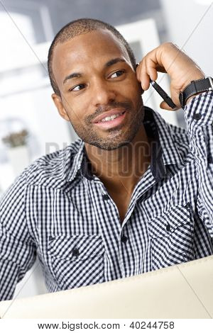 Portrait of handsome Afro-American guy speaking on cellphone, smiling.