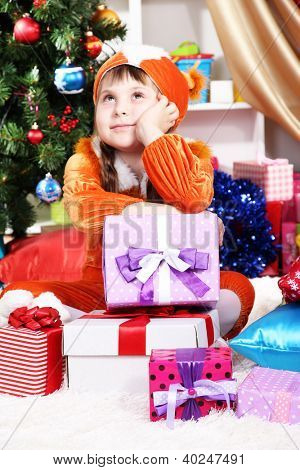 Dreaming little girl in suit of squirrels surrounded by gifts in festively decorated room