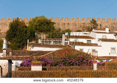 Medieval houses in the ancient city of Obidos, Portugal with castle walls  in the background