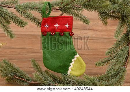 Meia de Natal com os presentes sobre o fundo de madeira