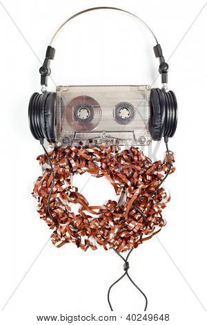Headphones on audio cassette with pulled out tape