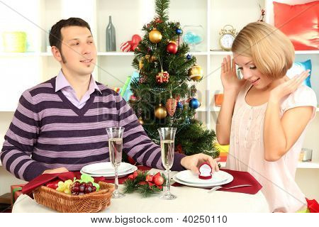 Young man makes proposal to marry girl at table near Christmas tree