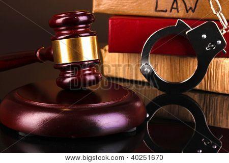 Martillo, esposas y libros sobre derecho aislado en primer plano negro