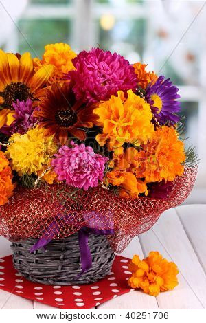Beautiful bouquet of bright flowers on wooden table on window background