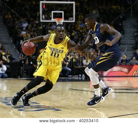 BROOKLYN-DEC 15: Michigan Wolverines guard Tim Hardaway Jr. (10) dribbles the ball past West Virginia Mountaineers guard Eron Harris (10) at Barclays Center on December 15, 2012 in Brooklyn.