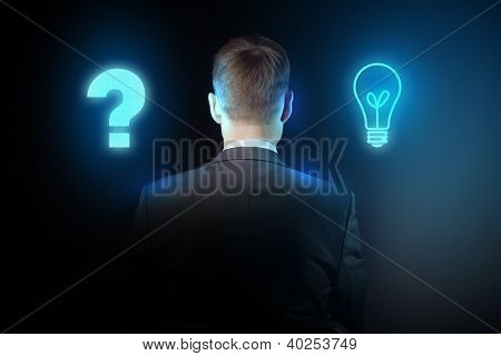 Senior businessman thinking and making choice while looking up