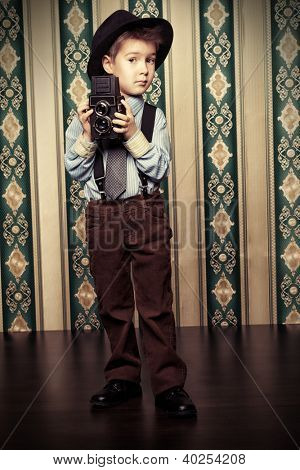 Little boy looking like a gentleman standing with a camera. Vintage background.