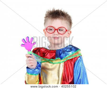 Little boy in big red glasses and clown costume holds toy hand and looks at it isolated on white background.