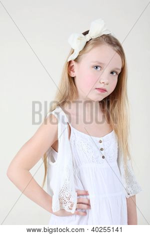 Little sorrowful girl in clean white dress with bow in her hair looks at camera.