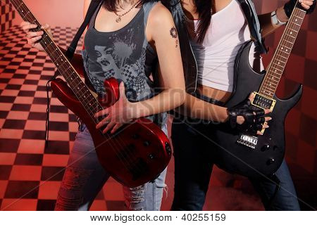 Part of bodies of two women playing electric guitar in studio with checkered background in red light and smoke.