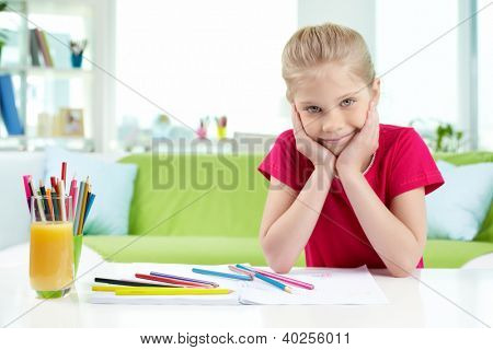 Portrait of lovely girl looking at camera while drawing with colorful pencils