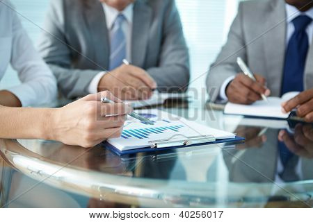 Close-up of human hand with pen pointing at paper while explaining something to colleagues
