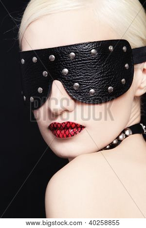 Portrait of young beautiful woman in studded blindfold