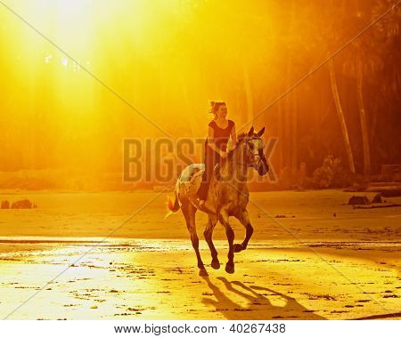 woman riding galloping horse on the beach at sunset