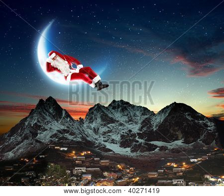 photo of santa claus sitting on the moon with a city and mountains below