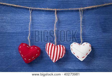 Three Textile Hearts Over Wooden Wall