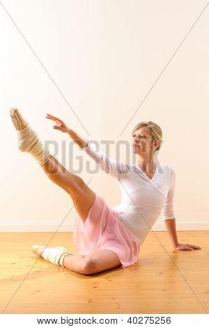 Beautiful ballet dancer lifting arm towards leg exercise woman ballerina