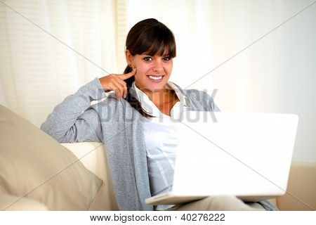 Smiling Woman Sitting On Sofa In Front Of Laptop