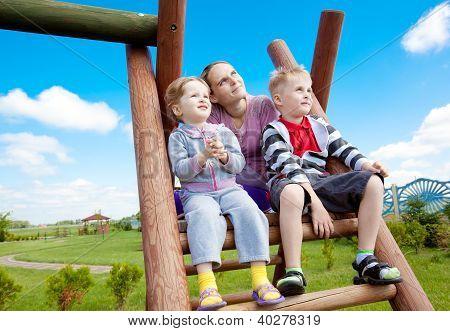 Família feliz no parque infantil