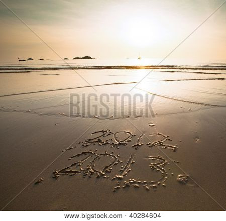 Conceptual: New Year 2013 is coming, inscription 2012 and 2013 on a beach sand