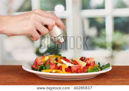 Hand adding salt using  salt shaker on bright background
