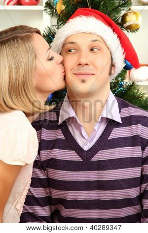Young happy couple near  Christmas tree at home