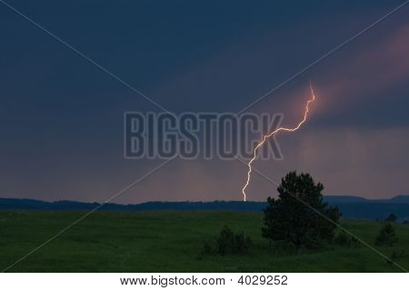 Single Lightning Bolt Over Meadow At Dusk